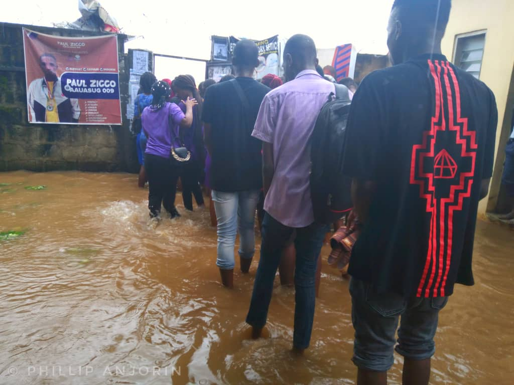 Students trying to leave through the gate amid rainfall.